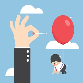 De hand duwende naald van de zakenman om de ballon te knallen