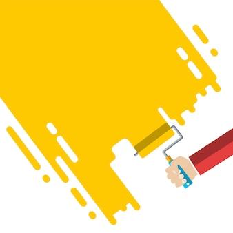 De hand van de mens houdt een verfroller vast met een gele kleur