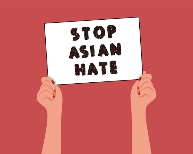 De hand van de vrouw houdt een witte banner vast met het bericht stop asian hate.