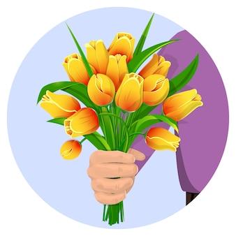 De hand van een man geeft een boeket van gele tulpen.