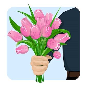 De hand van een man geeft een boeket van roze tulpen.