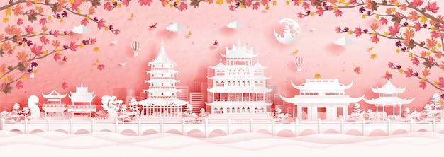 De herfst in hangzhou, china met dalende esdoornbladeren en wereldberoemde oriëntatiepunten in papier snijden stijlillustratie