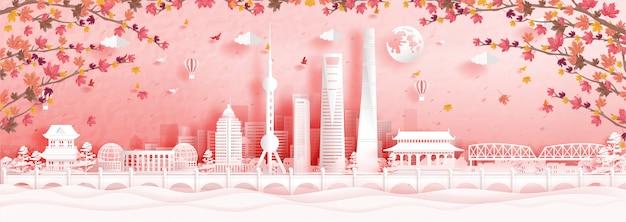 De herfst in shanghai, china met dalende esdoornbladeren en wereldberoemde oriëntatiepunten in papier snijden stijlillustratie