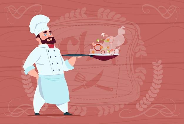 De holdingspan van de chef-kokkok met heet voedsel glimlachend beeldverhaal in wit restaurantuniform over houten geweven achtergrond