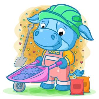 De illustratie van de blauwe koe trekt de roze kruiwagen