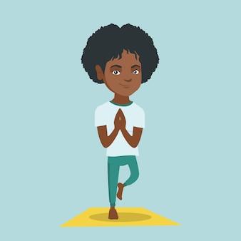 De jonge afrikaanse vrouw het praktizeren yogaboom stelt.