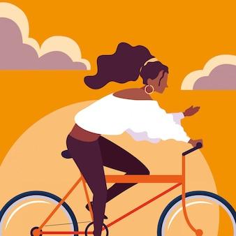 De jonge berijdende fiets van vrouwenafro met hemelsinaasappel