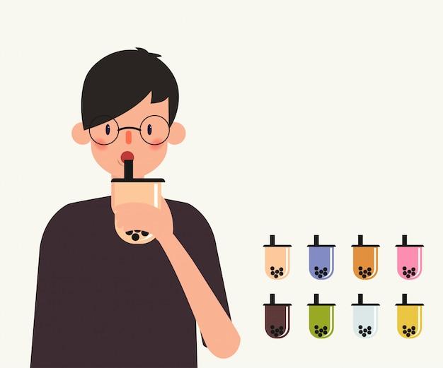 De jonge mens drinkt de thee van de bellenthee.