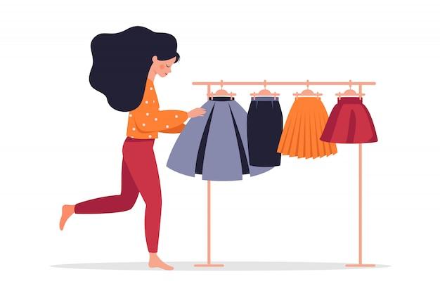 De jonge vrouw kiest een rok van kleurrijke rokken die op een hanger hangen