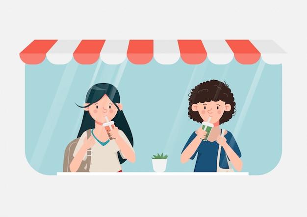 De jonge vrouwen drinken bellenmelkthee in koffiewinkel.