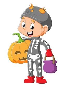 De jongen draagt het bottenkostuum en houdt de schrikpompoen van illustratie vast