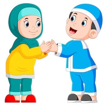 De jongen en het meisje geven de groet van ied mubarak