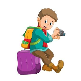 De jongen houdt de camera vast en zit op de koffer ter illustratie