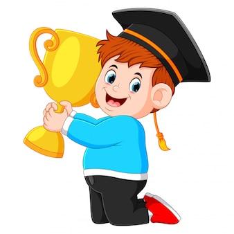 De jongen houdt de trofee op zijn afstudeerdag