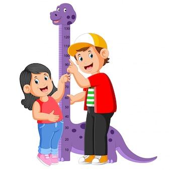 De jongen meet zijn zus op de hoogte van de dinosaurusmaat