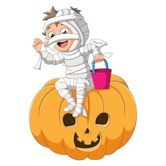 De jongen met het mummiekostuum zit op de enge pompoen van de illustratie