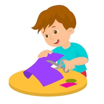 De jongen snijdt kleurendocument met schaar
