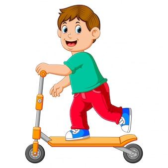 De jongen speelt op de oranje scooter