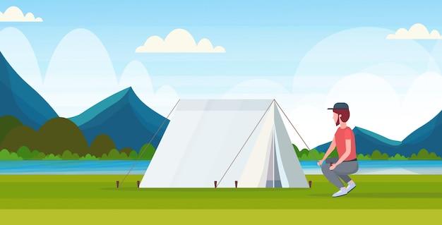 De kampeerder die van de mensenwandelaar een tent installeren die voor het kamperen de reiziger van het wandelingsconcept voorbereidingen treffen op van het de bergenlandschap van wandelings mooie rivier horizontale volledige lengte als achtergrond