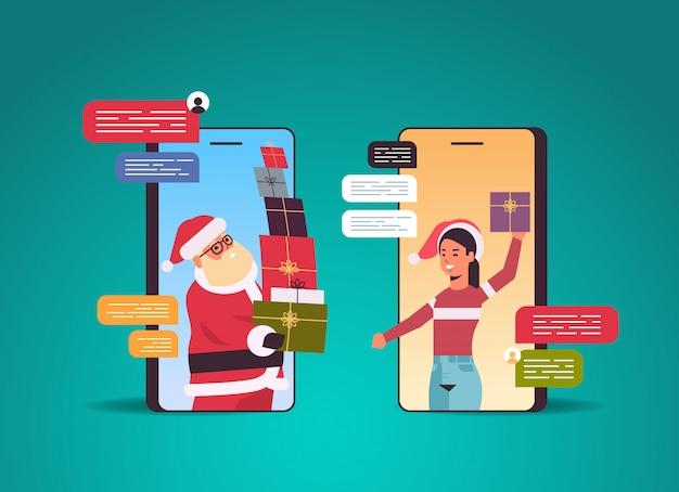 De kerstman die giftdozen geeft aan vrouw die babbelend app sociaal netwerkcommunicatie kerstmis vakantie vieringsconcept gebruiken