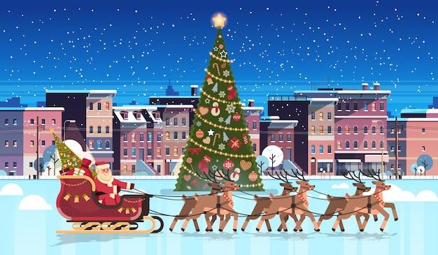 De kerstman in slee met rendieren verfraaide dichtbij sparrenstad de bouwhuizen