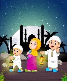 De kinderen houden de ramadanlantaarn onder het maanlicht