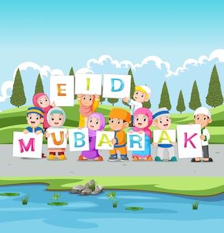De kinderen houden het ied mubarak-bord bij de rivier