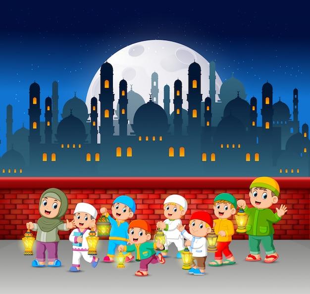 De kinderen lopen en houden de ramadanlantaarn bij de rode muur