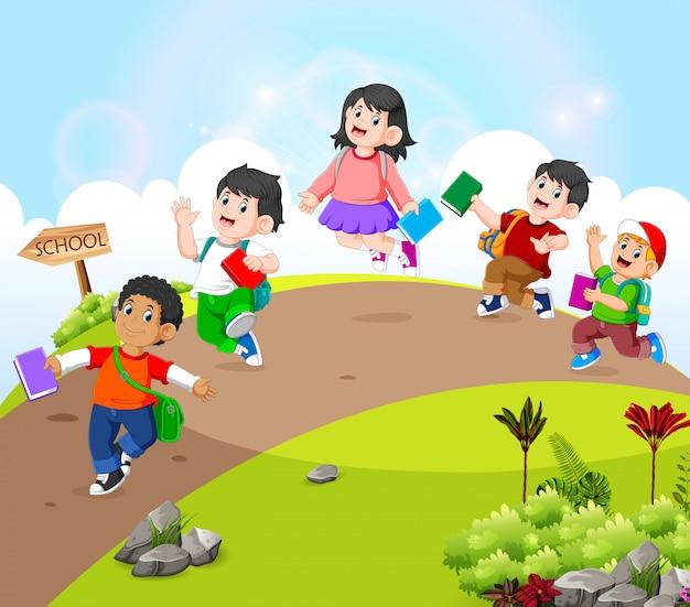 De kinderen lopen op de weg naar school gaan