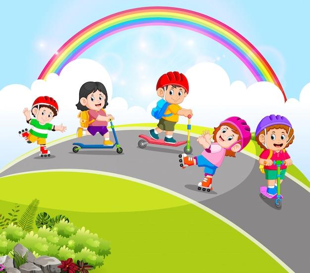 De kinderen spelen met de scooter en rolschaatsen op de weg