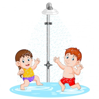 De kinderen spelen onder de douche
