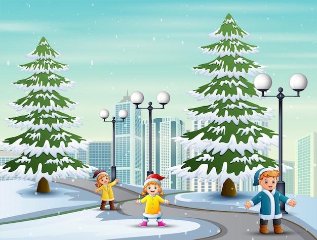 De kinderen spelen op de besneeuwde weg