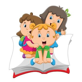 De kinderen zitten op het grote boek en zwaaien met de illustratie