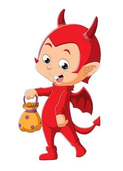 De kleine duivelsjongen houdt een mand vast voor de snoepjes ter illustratie