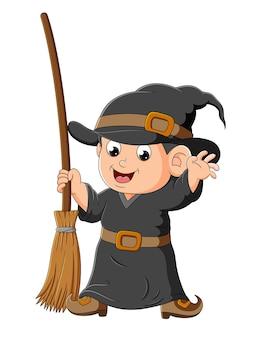 De kleine heksenjongen houdt de magische bezem van de illustratie vast