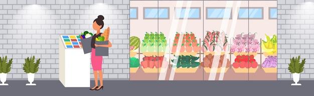 De kruidenierswinkelzakken van de vrouwenholding huisvrouw die zich bij zelfbedieningskassa het winkelen concept bevinden moderne supermarkt die buiten volledige lengte horizontaal bouwen