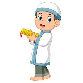 De lange jongen staat en houdt de koran vast met zijn handen