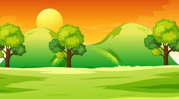 De lege scène van het weidelandschap in zonsondergangtijd