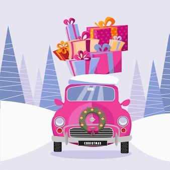 De leuke roze retro auto die met een kroon van kerstmis wordt verfraaid draagt gift kleurrijke dozen