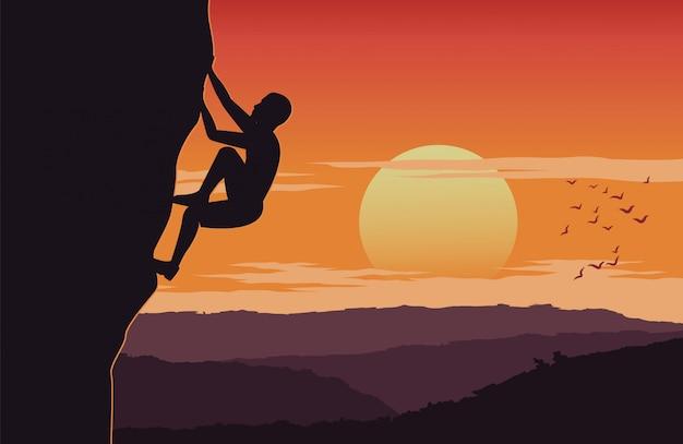 De mens beklimt omhoog klip op zonsondergangtijd