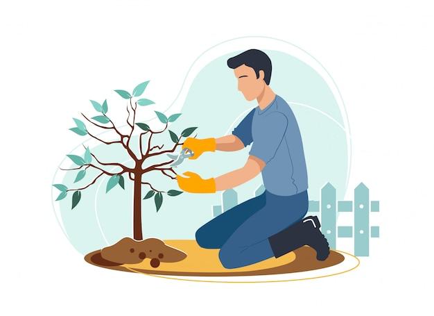 De mens is het snijden van boomtakken op zijn achtertuin in handschoenen en laarzen in de buurt van het hek. tuinieren hobby.