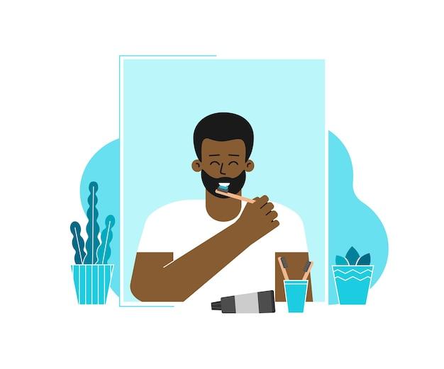 De mens maakt tanden schoon met tandenborstels, plakken. guy staat voor de spiegel, glimlacht