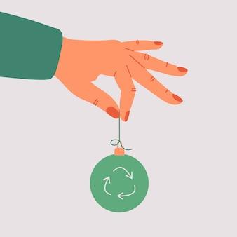 De menselijke hand houdt een groen xmas-speelgoed met een recyclingssymbool.
