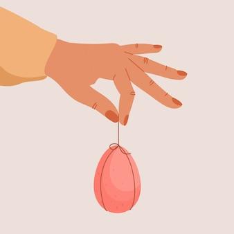 De menselijke handen houden pasen verfraaid ei. chocolade kleurrijk ei