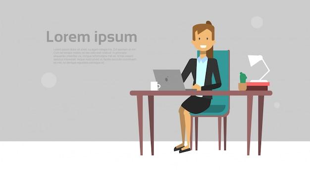 De moderne bedrijfsvrouw die aan laptop werkt zit bij bureau