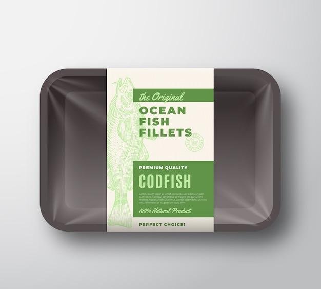 De originele visfilets abstract verpakkingsontwerp label op plastic bakje met cellofaan deksel. moderne typografie en handgetekende kabeljauw silhouet achtergrond lay-out.