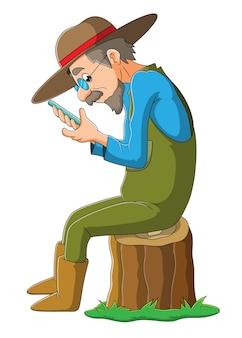De oude boer speelt de mobiele telefoon ter illustratie