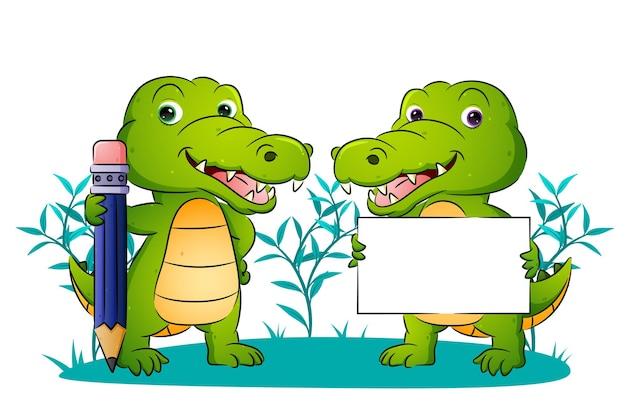 De paarleerling van de krokodil houdt het potlood en het lege bord met illustratie vast