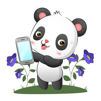 De panda toont een nieuwe smartphone in de tuin met de vrolijke gezichtsillustratie