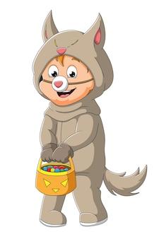 De schattige jongen met het wolvenkostuum houdt de mand met snoepjes ter illustratie vast